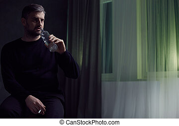 Man drinking and smoking - Middle-aged man drinking and...