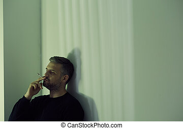 Man holding a cigarette - Depressed thoughtful man holding a...