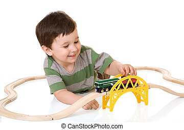 Boy playing with a train set, isolated white