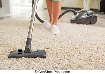 Housewife making soft rug clean - Woman is hoovering carpet...