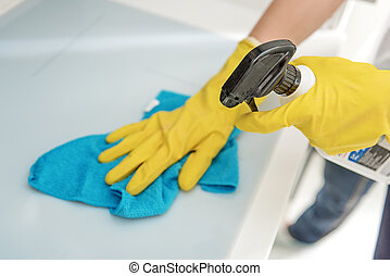Woman working with special detergent - Housewife in yellow...