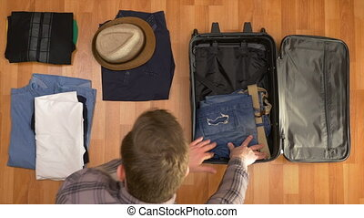 Top view travel concept of man organizing clothes into...