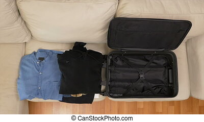 Top view timelapse of packing clothes into a suitcase
