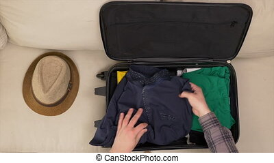 Man finishing packing clothes into a travel bag