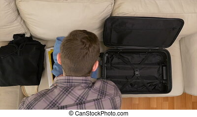 Top view of man packing clothes into travel bag