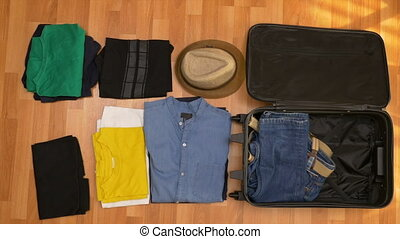 Top view timelapse of young man folding clothes in travel...