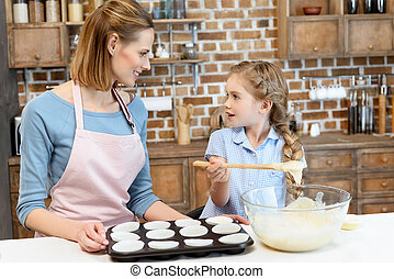 Happy mother and daughter baking cookies and looking at each other