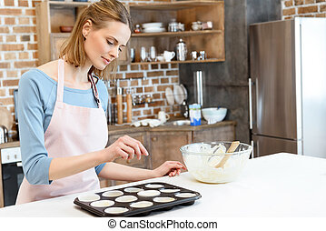 Smiling young woman in apron preparing form for baking cookies