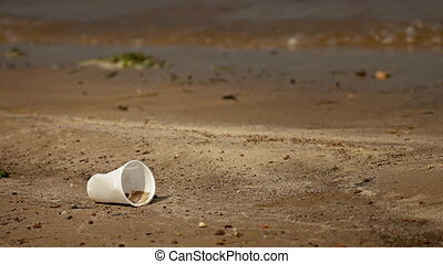 Discarded Plastic Cup on a Poluted River Bank. - Discarded,...