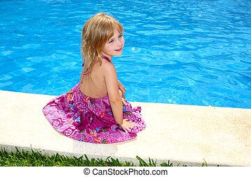 Little blond girl sitting smiling swimming pool