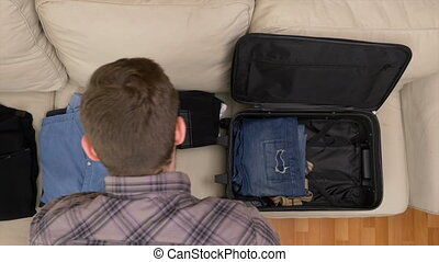 Top view timelapse of man packing clothes into a suitcase