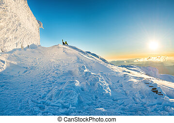 Two people looking at sunset from the top of winter mountain...
