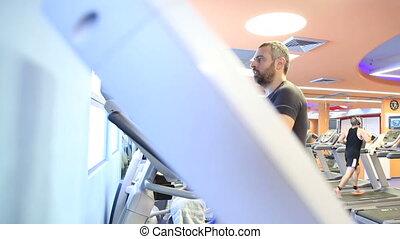 Slider on man using elliptical equipment - Shot of Slider on...