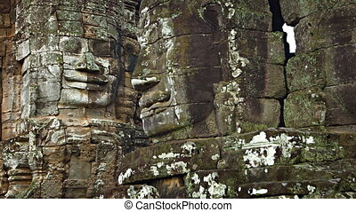 Stone faces on the walls of an ancient temple. Bayon temple,...