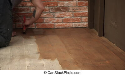 Man squatting on the wooden floor paint a broad brush in...