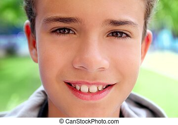 boy teenager closeup face macro happy smiling outdoor green...