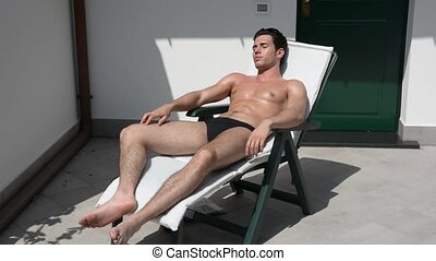 Young Man Sunbathing on Lounge Chair Reading Book -...