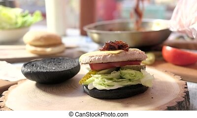 Cheeseburger with black buns. Patty and onion jam. Most...
