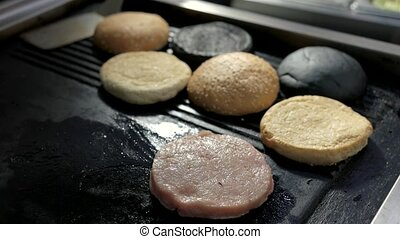 Pan with raw burger meat. Sliced sesame buns. Fry to the...