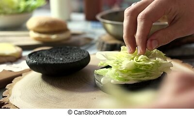 Dark burger bun and lettuce. Man making a sandwich.