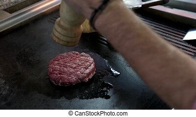 Raw burger patty and buns. Male hand with pepper grinder....