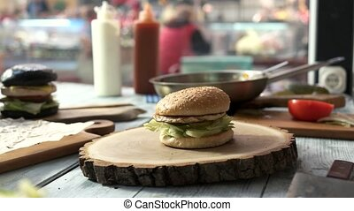 Different burgers on the table. Hamburgers and wooden...