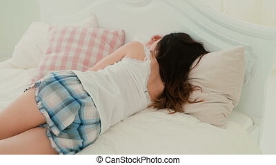Young woman in pajamas lying on the bed. Sleepy girl relaxing, having rest in the morning at home. Slow motion.