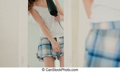 Young woman singing in bedroom, looking at mirror on the...