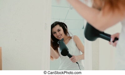 Happy young woman singing in bedroom, looking at mirror at reflection. Girl uses hair dryer and dances. Slow motion.