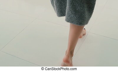 Close-up view to woman walking through the room. Girl takes...