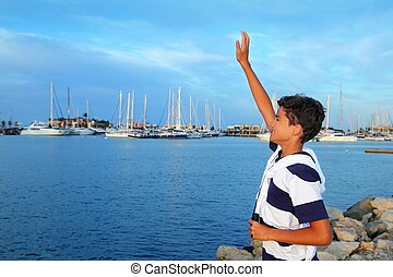 farewell boy rising hand up goodbye in boats marina -...