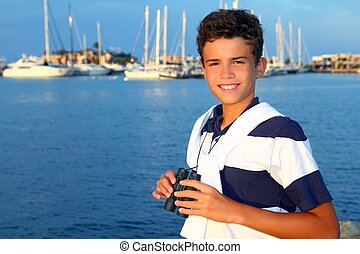 binoculars teenager boy on boat marina in blue summer...