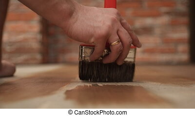 close-up of worker hand using brush paint wood in house...