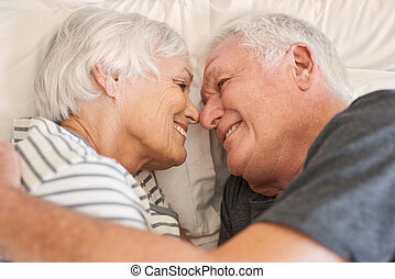 Devoted senior couple smiling warmly at each other in bed