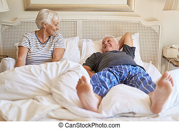 Happy senior couple relaxing on their bed in the morning -...