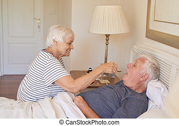 Senior woman giving medicine to her sick husband in bed