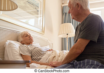 Senior man taking care of his sick wife in bed - Sick senior...