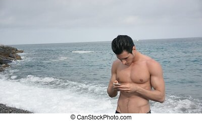 Young man at beach talking on cell phone - Young man at the...