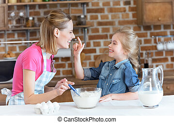 portrait of cheerful mother and daughter having fun while cooking