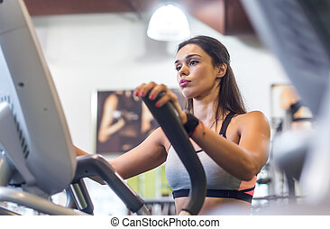 Fit woman exercising at fitness gym aerobics elliptical...