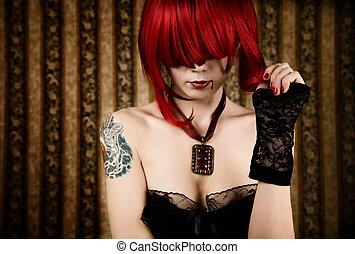 Redhead vampire with drop of blood, glamour background