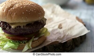 Beef burger with sesame seeds. Grilled cheese, meat and...