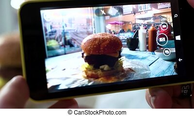 Cell phone photographing a burger. Hamburger on cafe table....