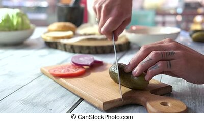 Male hands cutting pickle. Sliced vegetables on wood board....