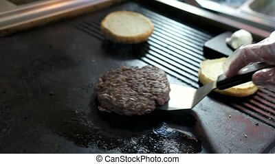 Patty and spatula. Meat and buns on pan. Juicy beef for...