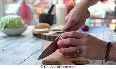 Hands cutting tomato on board.