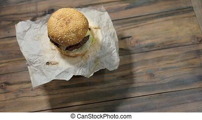 Cheeseburger on wood background. Burger and wax paper....