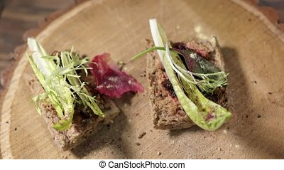 Two sandwiches on wooden board. Duck meat and onion jelly....