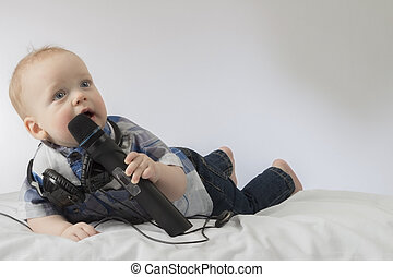 Funny baby boy singing karaoke. Lying infant kid with microphone and headphones. Concept for advertising of karaoke club