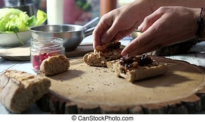 Hands making sandwiches. Caramelized onions and fresh...